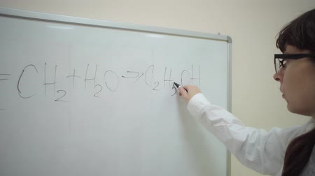 tlen : Chemical student corrects mistake in general chemical formula for hydrating ethylene with black marker on blackboard. Ethanol Production Study.