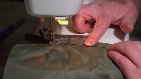 tecido : Close-up hands of an elderly woman are processing the edge of a clothing detail using a sewing machine. The needle pierces a dense waterproof khaki fabric.