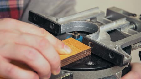 madeira compensada : Close-up of the milling cutter works on small wooden plank with large amount of sawdust, the carpenters hands chamfering the edge of the board made of glued plywood. Stock Footage
