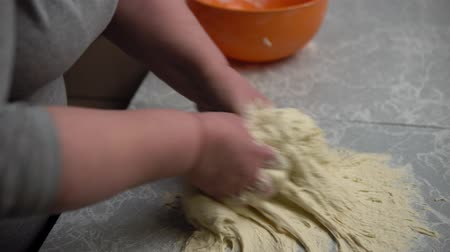 滋養物 : Close-up of female hands kneading dough on the kitchen table at home, grandma makes homemade baking for her family.