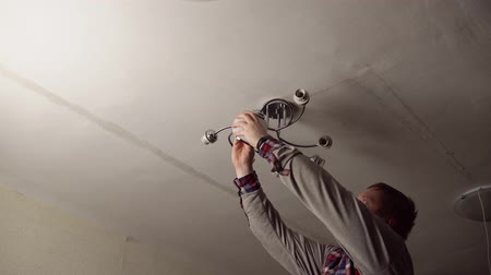 schroef : Red-bearded electrician in plaid shirt installs new chandelier on the white ceiling in the room.The master screws glass shade to the base of the fixture.