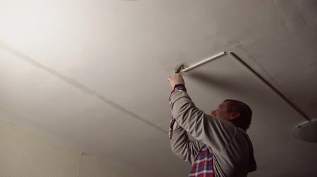 монтаж : A red-bearded electrician in a checked shirt with a screwdriver screws a metal base to the ceiling to install a new chandelier in the room.
