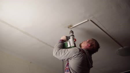 schroef : Strong red-bearded electrician with rotary hammer drills hole in the ceiling to install new chandelier. The concept of home repair.