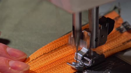 khaki : Close-up hands of an elderly woman sew an orange zipper to khaki cloth on a modern electric sewing machine.