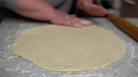 スプレッド : Close up faceless plump older woman spreads raw round dough on a table in the kitchen. The process of making homemade cakes.
