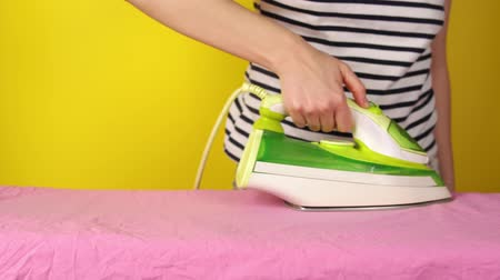 гладильный : A faceless young woman with an iron smoothes a pink sheet on an Ironing Board standing next to a yellow wall.