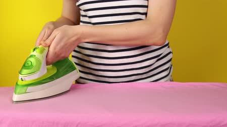 гладильный : Young woman smoothes wrinkles on the bed linen and dances.Faceless girl with iron smoothes pink sheet on ironing board standing next to yellow wall. Стоковые видеозаписи