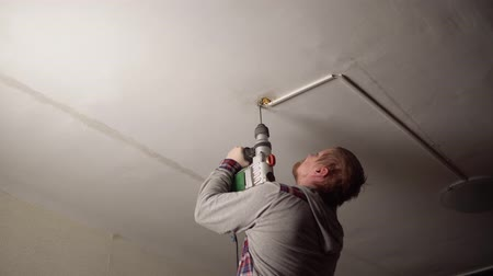 再建 : Strong male electrician in gray shirt with rotary hammer drills hole in the ceiling to install and connect the chandelier to electricity. 動画素材