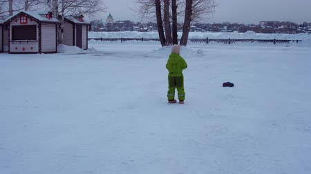 miniatűr : Cute child in a green jumpsuit controls remote-controlled electric toy Off road monster truck car in snowy park in winter. Stock mozgókép
