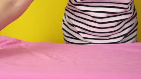 crumpled : Close-up of faceless young woman adjusting a crumpled pink sheet, preparing for Ironing with an iron. Hands lift the fabric and move it along the Board.