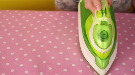 гладильный : Close-up of female hand with green iron smoothes pink bed linen with white circles on ironing board.