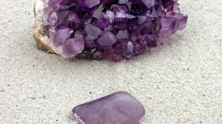 исцелять : Amethyst, rough and smooth, processed and unprocessed, polished and raw, purple crystals on sand