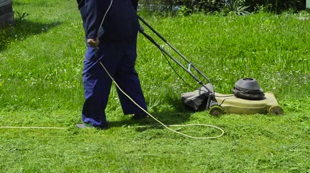 yards : Man mowing the grass with old electric grass cutter, moving backwards   Stock Footage