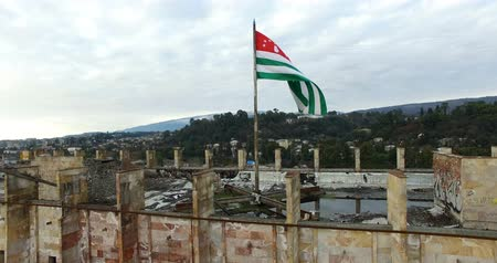 pošta : the city landscape with the destroyed building over which the Abkhazian flag is flying. Dostupné videozáznamy