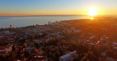 aerial survey of the urban landscape with a beautiful sunset over the sea.