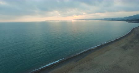 coastline with long sandy beach and sea on the background of gloomy spring sky Wideo