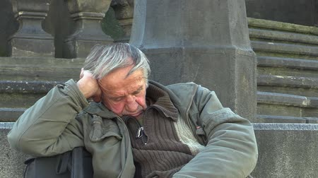 hobo : Authentic emotion homeless man senior asleep and awakening, Europe