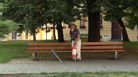 инвалидность : Handicapped homeless man senior on crutches from leaving the park, the town of Olomouc, Europe