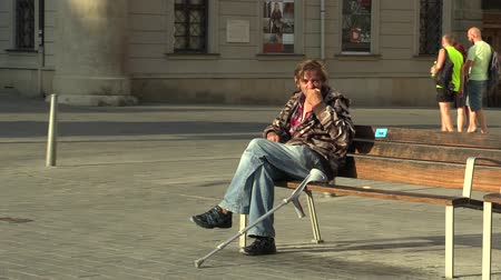 evsiz : Authentic emotion handicapped homeless man sitting on a bench and eating, town Brno, Europe, EU Stok Video