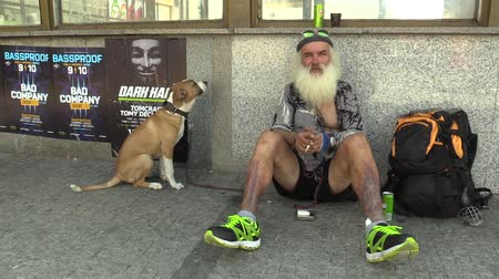 hobo : BRNO, CZECH REPUBLIC - SEPTEMBER 1, 2015: Authentic emotion homeless man sitting with dog, town Brno, South Moravia, Czech Republic, Europe, EU