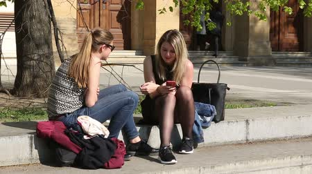 bejárat : BRNO, CZECH REPUBLIC, APRIL 15, 2017: Authentic students beautiful girls University in Brno sitting and talking before school, girls, boy, authentic spring, Czech Republic, Europe, EU Stock mozgókép
