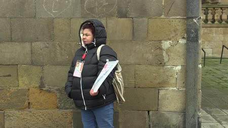 Çingene : OLOMOUC, CZECH REPUBLIC, JANUARY 24, 2017: A woman selling a magazine Novy Prostor or Street News on the street, helping homeless people and people in poverty in social distress, first sold in the US Stok Video