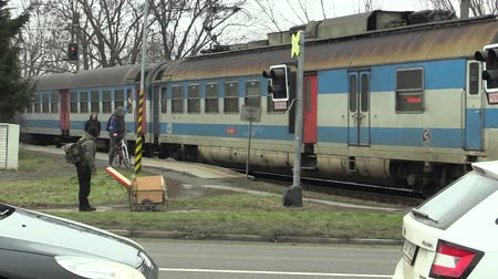 isteyen : OLOMOUC, CZECH REPUBLIC, JANUARY 18, 2018: Train in poor technical condition and very old, passes at the crossing in Olomouc, people waiting, warning sign on the traffic lights