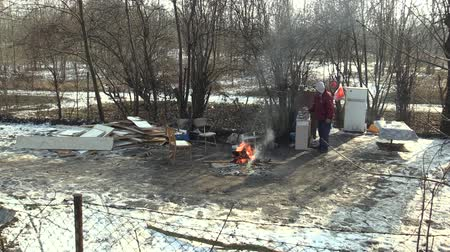 шале : OLOMOUC, CZECH REPUBLIC, JANUARY 29, 2018: Homeless poor burning wood board and creating fire to warm themselves in the winter snow, emit the radio and start, living in a sheet wood metal chalet Стоковые видеозаписи