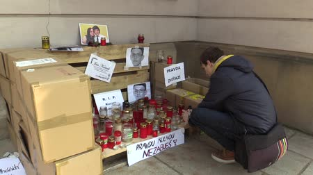 associated : OLOMOUC, CZECH REPUBLIC, MARCH 1, 2018: A memorial place with burning candles and photographs of murdered Slovakian journalist Jan Kuciak, man ignites candles with authentic situation