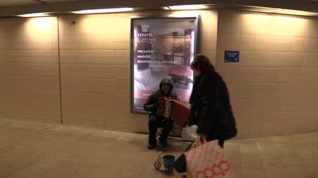 Çingene : OLOMOUC, CZECH REPUBLIC, MARCH 5, 2018: Gypsy man in city begging money into a cup, authentic plays music the accordion harmonica, gipsy and tzigane culture, people throw money on a beggar