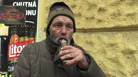evsiz : OLOMOUC, CZECH REPUBLIC, MARCH 5, 2018: An authentic poor homeless drinking alcohol rum in glass bottles. Very real, life on the street, the civilization problem of the company alienation and poverty. Stok Video