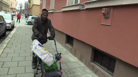 holding steady : OLOMOUC, CZECH REPUBLIC, MARCH 5, 2018: An authentic poor homeless man walks steadycam down the street with a cart carriage in which he holds a bottle plastic of wine. Very real, life on the street