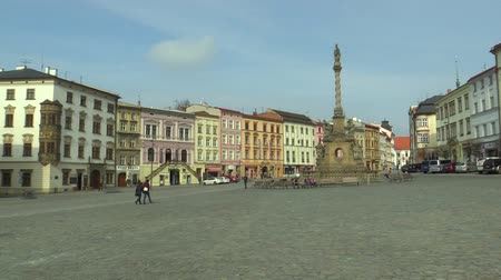 marian : Baroque plague column called Marian on the Dolni square in the city of Olomouc. National cultural monument from 1723, architect Jan Sturmer, people walk and sit on bench, historical houses monument