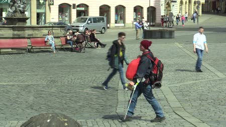 kule : OLOMOUC, CZECH REPUBLIC, APRIL 12, 2018: Handicapped man with a backpack on his back has a severe disability and goes to the French crutches, limp on walking, very stressed, people invalid