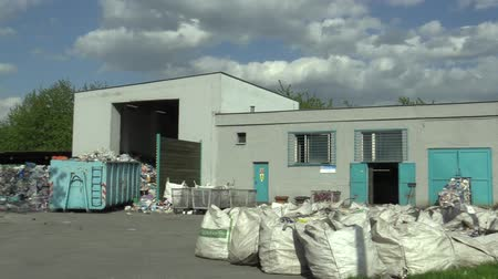 litter box : OLOMOUC, CZECH REPUBLIC, APRIL 25, 2018: Building house line for industrial sorting of types of plastics waste. They are sorting on green and white PET bottles, plastic bags and carton, recycling Stock Footage