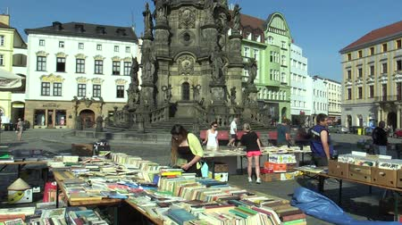 книжный магазин : OLOMOUC, CZECH REPUBLIC, APRIL 30, 2018: Sale of books on the square marketplace market in the city of Olomouc in the background UNESCO heritage plague column Holy Trinity, people are buying