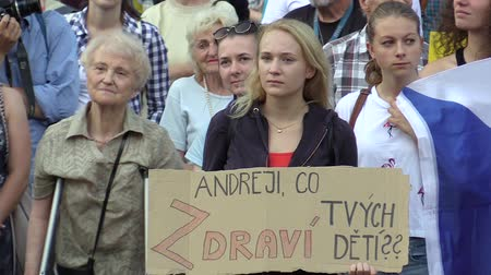 know : OLOMOUC, CZECH REPUBLIC, MAY 15 , 2018: Demonstration of people crowd against the Prime Minister Andrej Babis and president Milos Zeman, a banner with Andrej, whats your kids health, young woman