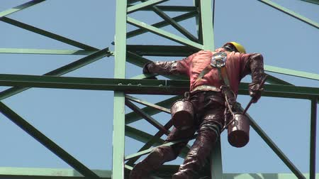 physically : OLOMOUC, CZECH REPUBLIC, APRIL 25, 2018: The male painter is painting an old steel column pole of high electrical voltage in red, buckets of paint and brush, physically very demanding height work