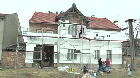 absorption : OLOMOUC, CZECH REPUBLIC, APRIL 12, 2018: Thermal insulation carried out by workers in a family house villa use slab insulation boards with low water absorption and high penetration resistance thermal