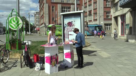 manipulacja : OLOMOUC, CZECH REPUBLIC, JULY 5, 2018: Young women offer for sale perfume cosmetics on the street to people, advertising and marketing, people can perfume smell Wideo