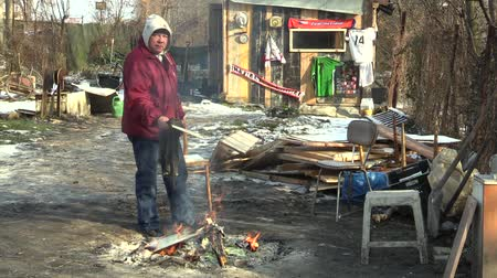 prejudicial : OLOMOUC, CZECH REPUBLIC, JANUARY 29, 2018: Homeless poor burning wood board and creating fire to warm themselves in the winter snow, wiping and cleaning the image, living in a sheet wood metal chalet Stock Footage