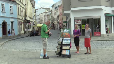 him : OLOMOUC, CZECH REPUBLIC, JULY 5, 2018: Jehovahs Witnesses religious society, two young women on the street offer books and newsletters about bible and teachings about God, free spread magazines Awake