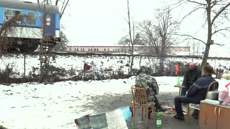 levou : OLOMOUC, CZECH REPUBLIC, JANUARY 29, 2018: Homeless burning and creating fire to warm themselves in the winter snow, departing train and tracks Vídeos