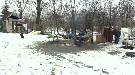levou : OLOMOUC, CZECH REPUBLIC, JANUARY 29, 2018: Homeless burning and creating fire to warm themselves in the winter snow, take things with outdoor cabinets Vídeos