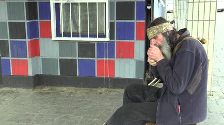 munch : OLOMOUC, CZECH REPUBLIC, MAY 5, 2018: Authentic emotion face homeless man in city, cigarette joint pack gives tobacco, burns fire a cigarette lighter, long beard and Indian scarf in her hair, poor man