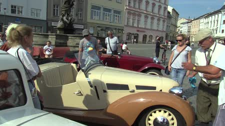 him : OLOMOUC, CZECH REPUBLIC, JULY 5, 2018: Historic car veteran on a public car ride through city of Olomouc drive people, Aero 30 1939, the old man polishes the car and people admire him