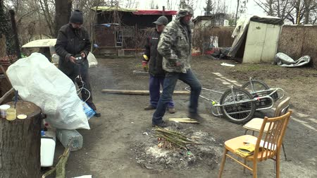 compares : OLOMOUC, CZECH REPUBLIC, MARCH 20, 2018: Homeless poor prepares ignites burning wood branch cracked and creating fire to warm themselves in the winter, living in a sheet wood metal chalet