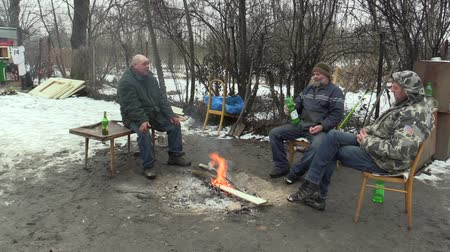 ситуация : OLOMOUC, CZECH REPUBLIC, JANUARY 29, 2018: Homeless men burning and creating fire to warm themselves in the winter snow, alcohol drinks wine, living in a sheet wood metal chalet Стоковые видеозаписи