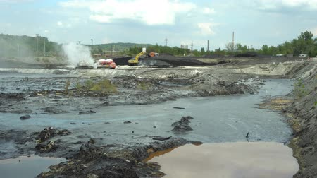 meio : OSTRAVA, CZECH REPUBLIC, AUGUST 28, 2018: Liquidation of remediation of landfills waste of oil and toxic substances, burnt lime is applied to the oil pollution by means of fine cutter excavator 4K