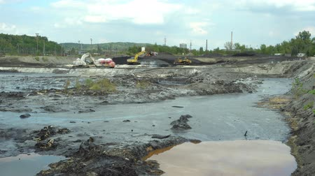 čeština : OSTRAVA, CZECH REPUBLIC, AUGUST 28, 2018: Liquidation of remediation of landfills waste of oil and toxic substances, burnt lime is applied to the oil pollution by means of fine cutter excavator 4K
